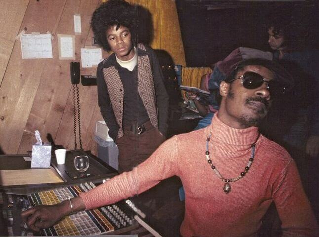 A very young Michael Jackson notes with admiration for a well at a young Stevie Wonder in the Motown studio